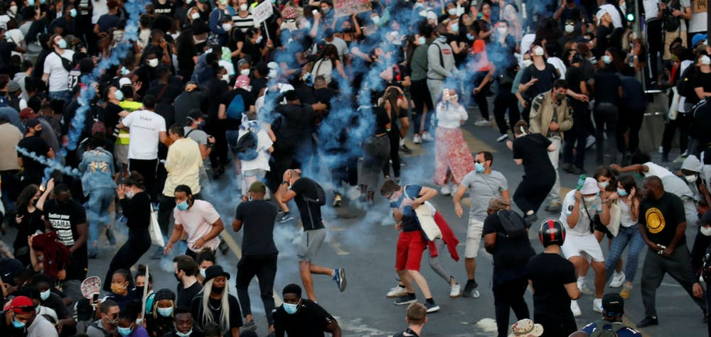 People run from tear gas as they attend a banned demonstration planned in memory of Adama Traore, a 24-year-old black Frenchman who died in a 2016 police operation which some have likened to the death of George Floyd in the United States, in front of courthouse in Paris, France June 2, 2020. REUTERS/Gonzalo Fuentes