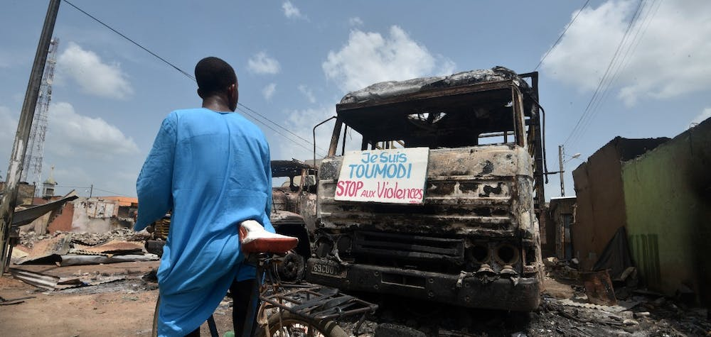 """A cyclist reads a sign on a burnt truck calling for violence to stop in the market of Toumodi on November 4, 2020, during a campaign of non-violence and peace awareness by young volunteers after inter-community clashes during the country's presidential election of October 31, 2020. - Ivory Coast is caught in a standoff after Ivorian President Alassane Ouattara won a third term by a landslide in October 31, 2020's vote, which was boycotted by the opposition claiming an """"electoral coup"""" in a nation with a constitutional two-term presidential limit. (Photo by SIA KAMBOU / AFP)"""
