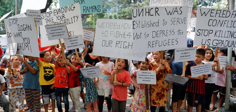 Displaced children hold placards as they take part on a protest outside UN Refugee Agency UNHCR's office in Jakarta, Indonesia, Octoer 10, 2019. REUTERS/Willy Kurniawan