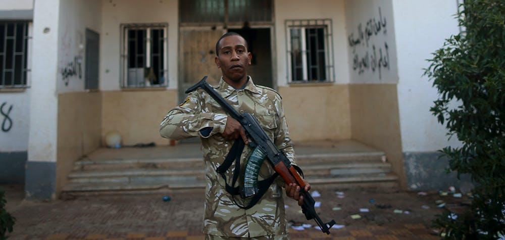 Un garde de sécurité armé se tient devant un poste de police à Benghazi, le 4 décembre 2014