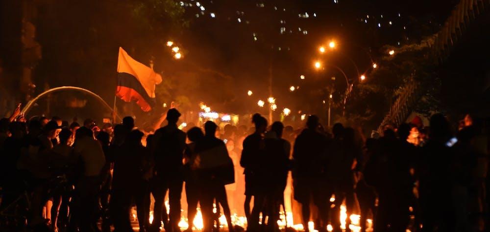 des manifestants sont rassemblés la nuit dans l'un des points de résistance de la ville de Cali, 2021