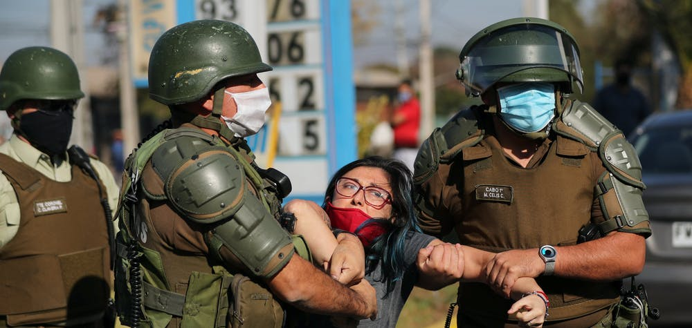 A woman is detained after shouting slogans against riot police at a poor neighborhood where people are protesting the lack of help from the government, during a general quarantine imposed due to a surge of fresh coronavirus disease (COVID-19) cases, at 'El Bosque' area in Santiago, Chile May 18, 2020. REUTERS/Ivan Alvarado