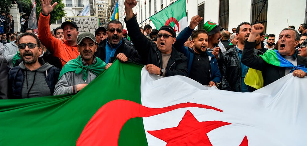 People chant slogans as they wave a large Algerian national flag during a weekly anti-government demonstration in the capital Algiers on March 6, 2020. - Protests against cronyism have continued in Algeria despite former president Abdelaziz Bouteflika's resignation and the election of a new president in December 2019.