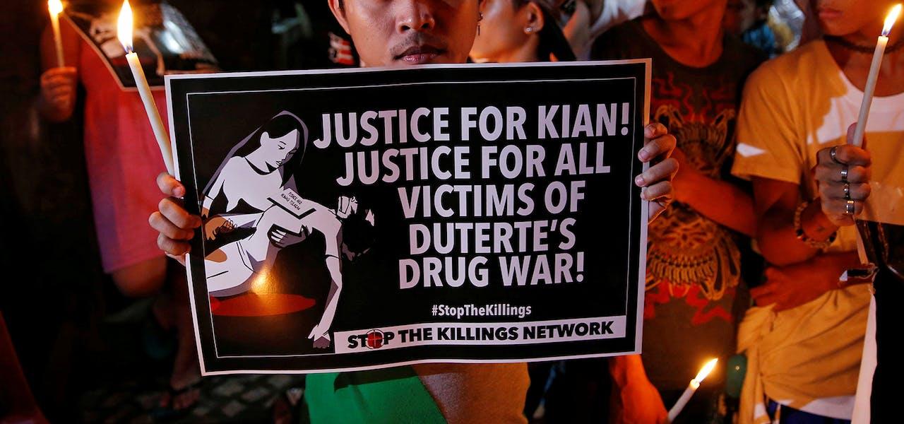 Des manifestants et des habitants tiennent des bougies allumées et des pancartes lors de la veillée funèbre de Kian Loyd delos Santos, un lycéen de 17 ans, qui faisait partie des personnes abattues à Manille en août 2017