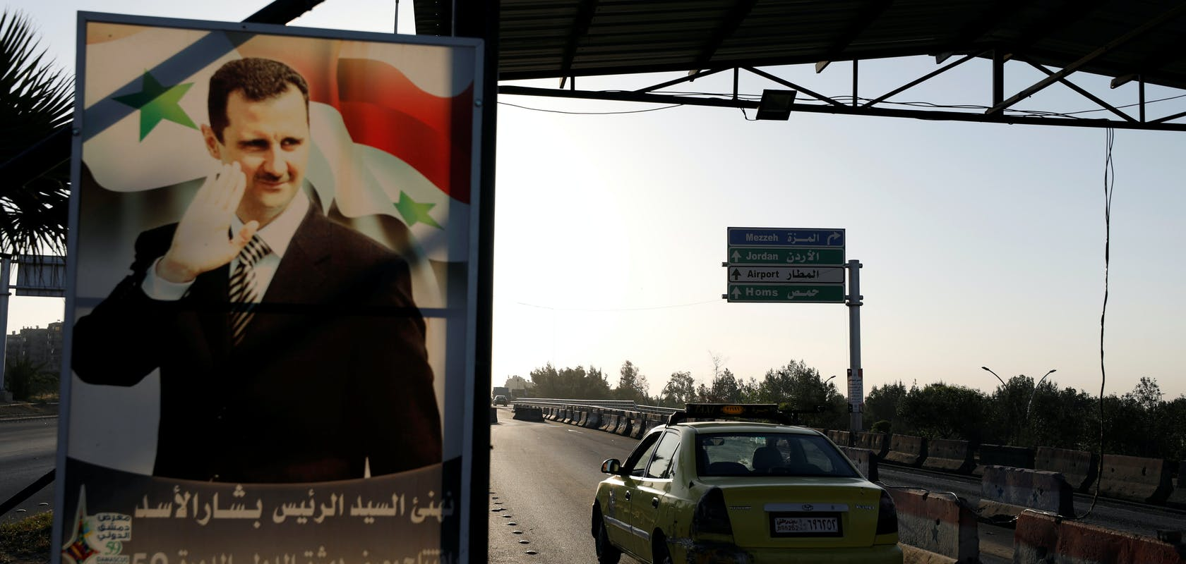 bbcb0d18-a9f4-469d-adeb-9736fb3655c9_A+poster+of+Syrian+President+Bashar+al-Assad+is+seen+on+the+main+road+to+the+airport+in+Damascus.JPG?auto=compress,format&rect=0,312,4918,2342&w=1680&h=800
