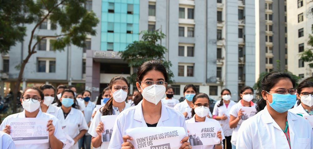 Des médecins internes tiennent des pancartes lors d'une manifestation pour réclamer une augmentation de salaire devant le GMERS Sola Medical College and Civil Hospital, en Inde, le 14 décembre 2020.