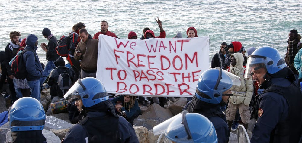Migrants and activists hold a banner as they face off with Italian police on the seawall at the Saint Ludovic border crossing on the Mediterranean Sea between Ventimiglia, Italy and Menton, France, September 30, 2015. A migrant camp on the French- Italian border was dismantled Wednesday morning by about 150 Italian carabinieri and police officers. REUTERS/Eric Gaillard TPX IMAGES OF THE DAY