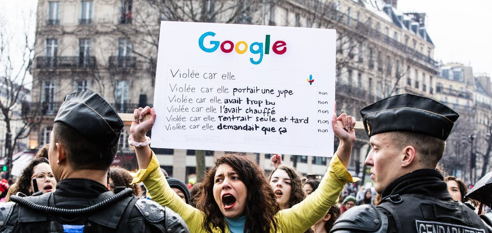 """A protester holds a sign with a google search with the reasons for a rape. Feminist demonstration on 8 March 2020 in Paris for the international day of struggle for women s rights, under the rallying cries """"Great winners"""", """"We all stop"""". Paris, France, Sunday, March 08, 2020."""