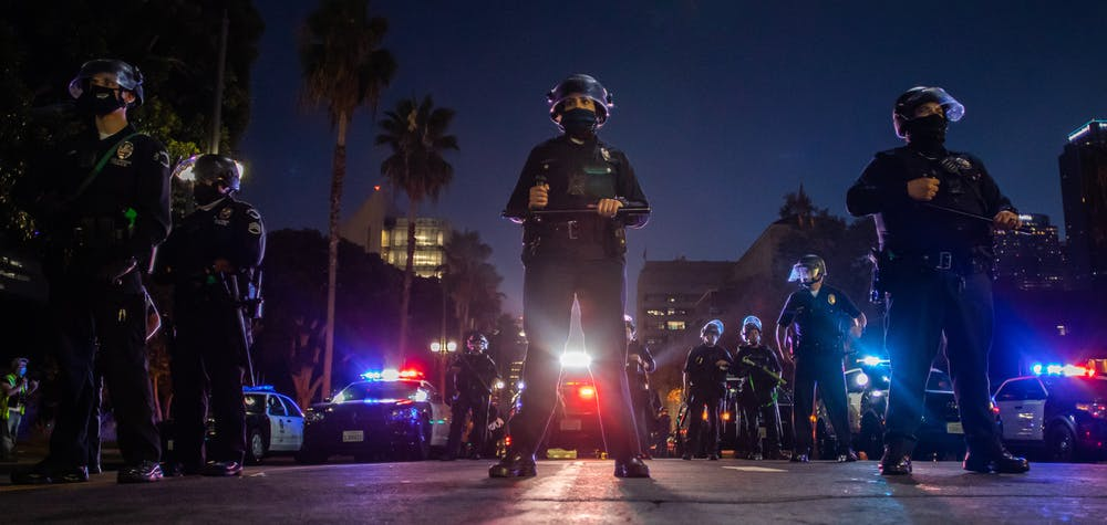 Police officers hold a line in front of LA City Hall during a protest demanding justice for George Floyd, Breonna Taylor and also in solidarity with Portland's protests, in Downtown Los Angeles, California, on July 25, 2020. (Photo by Apu GOMES / AFP)