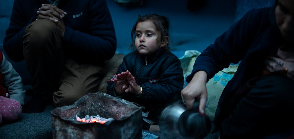 Marjan Hosini, 3, warms her hands over hot coal as Yasamin, 25, Hosini's mother, pours tea into cups inside their temporary shelter at a makeshift camp for refugees and migrants next to the Moria camp, on the island of Lesbos, Greece, February 16, 2020. REUTERS/Alkis Konstantinidis