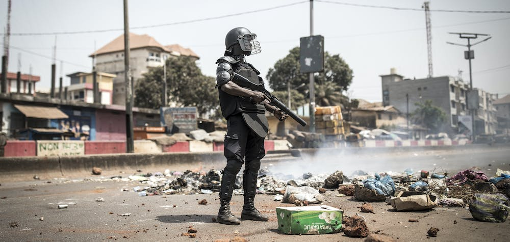 """A policeman stands along the """"axis of democracy"""" as protests broke out in Conakry on February 29, 2020. - Guinea's President Alpha Conde announced on February 28, 2020 a """"slight postponement"""" of March 1's referendum on whether to adopt a new constitution, following mounting international criticism over the poll's fairness. (Photo by JOHN WESSELS / AFP)"""