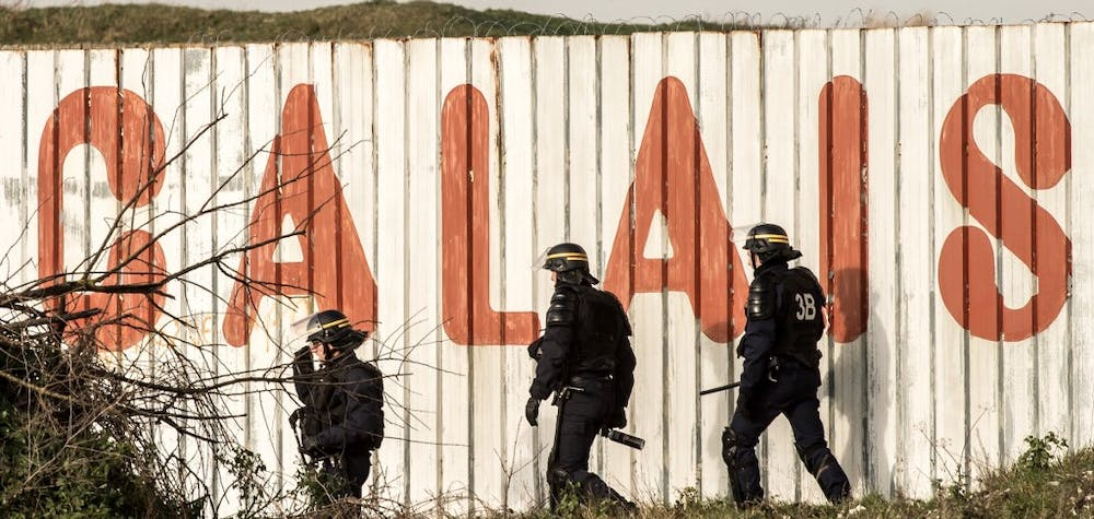 """French riot police officer walk in front of a fence with the lettering 'Calais' near the A16 motorway near the site of the Eurotunnel in Coquelles, near Calais, northern France on January 21, 2016. - Approximately 300 migrants have tried to board trucks protected by French police, according to an estimate made by an AFP photographer present at the scene. Clashes already erupted briefly on the night of January 20 at the port bypass Calais between several hundred migrants and security forces, who fired tear gas to restore the situation, according to an AFP correspondent. These incidents occurred after the prefecture of Pas-de-Calais had set an ultimatum which expired early in the afternoon for the last migrants to leave a deforested 100 metre strip of the """"Jungle"""" camp along the ring road for safety reasons. (Photo by PHILIPPE HUGUEN / AFP)"""