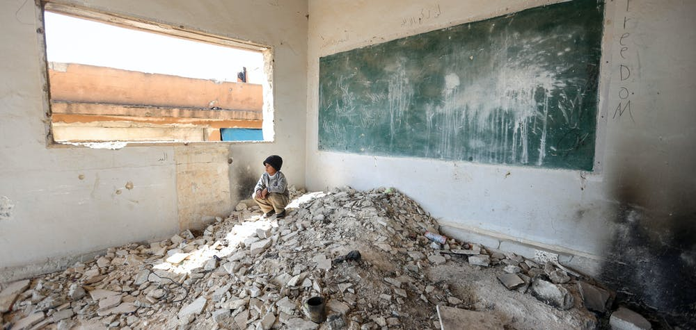 IDLIB, SYRIA - AaPRIL 02: A Syrian kid is seen amid the ruin of a school after displaced by bombardments of Assad Regime and its supporter Russia in Idlib, Syria on April 02, 2020. Sixteen Syrian families take shelter in two school ruins in the north eastern district of the city.