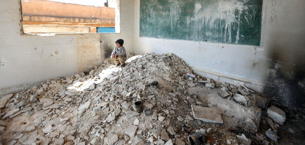 IDLIB, SYRIA - APRIL 02: A Syrian kid is seen amid the ruin of a school after displaced by bombardments of Assad Regime and its supporter Russia in Idlib, Syria on April 02, 2020. Sixteen Syrian families take shelter in two school ruins in the north eastern district of the city.