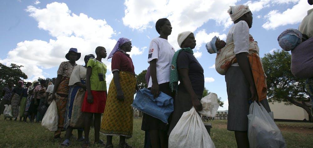 Des villageois zimbabwéens collectent leurs rations mensuelles d'aide alimentaire à l'école primaire de Rutaura, dans le district de Rushinga, à Mt darwin Plus de 6 millions de personnes en Angola, au Lesotho, au Malawi et au Zimbabwe risquent de souffrir de graves pénuries alimentaires en raison de cycles répétés de sécheresse et d'inondations, a déclaré lundi la FICR, l'organisation humanitaire mondiale. La Fédération internationale des sociétés de la Croix-Rouge et du Croissant-Rouge a déclaré que la crise passait largement inaperçue dans le monde extérieur et que ses appels au soutien financier n'avaient obtenu qu'un soutien limité. REUTERS/Philimon Bulawayo (ZIMBABWE - Tags : POLITIQUE SOCIÉTÉ)