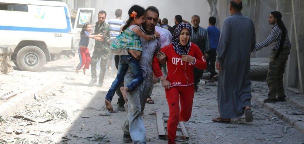 Une famille syrienne court pour se mettre à l'abri parmi les immeubles ruinés après un bombardement à Alep. 29/04/2016