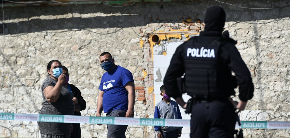 People wearing protective face masks are pictured as a police officer looks on while the coronavirus disease (COVID-19) spreads in the area around Roma settlements, in Zehra, Slovakia April 9, 2020.