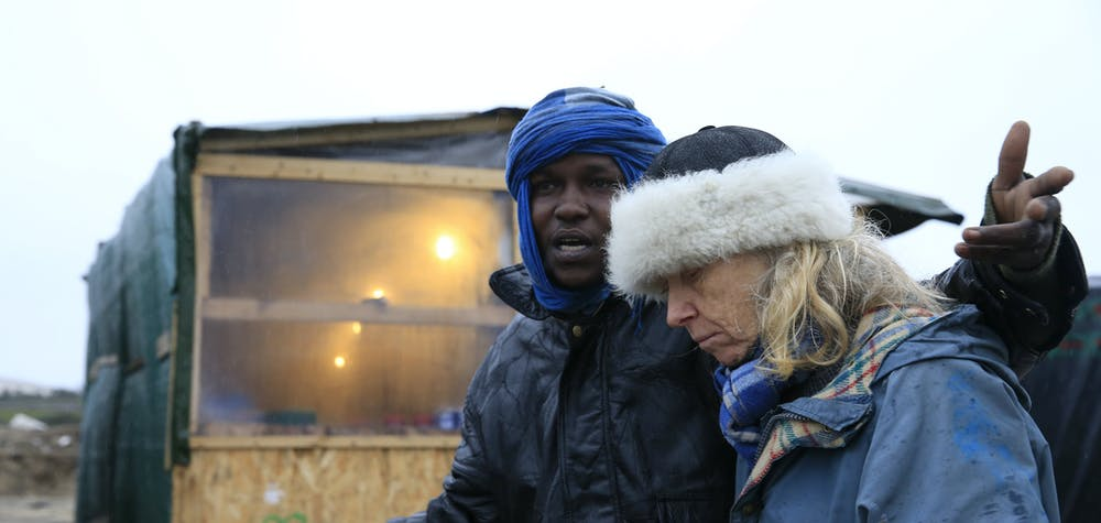 """Maya (R), a volunteer with """"Auberge des Migrants"""", listens to Muhammad, a migrant from Sudan, who lives in  the southern part of a camp for migrants called the """"jungle"""", during a rainy winter day in Calais, northern France, February 22, 2016.  French authorities have asked migrants living in tents and makeshift shelters in the southern sector of the """"jungle"""", to leave the area.  REUTERS/Pascal Rossignol"""