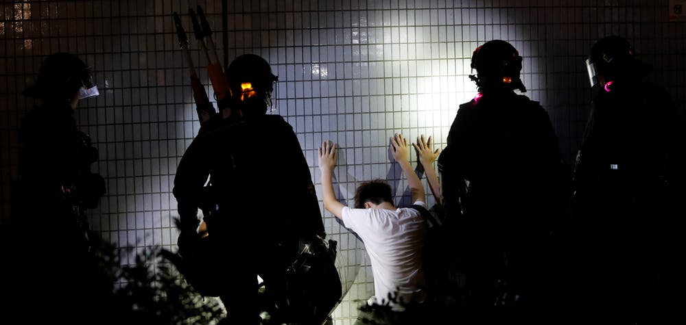 Men detained by riot police kneel by a wall after a protest at Yuen Long station against violence that happened two months ago when white-shirted men wielding pipes and clubs wounded both anti-government protesters and passers-by, in Hong Kong, China September 21, 2019. Picture taken September 21, 2019. REUTERS/Tyrone Siu