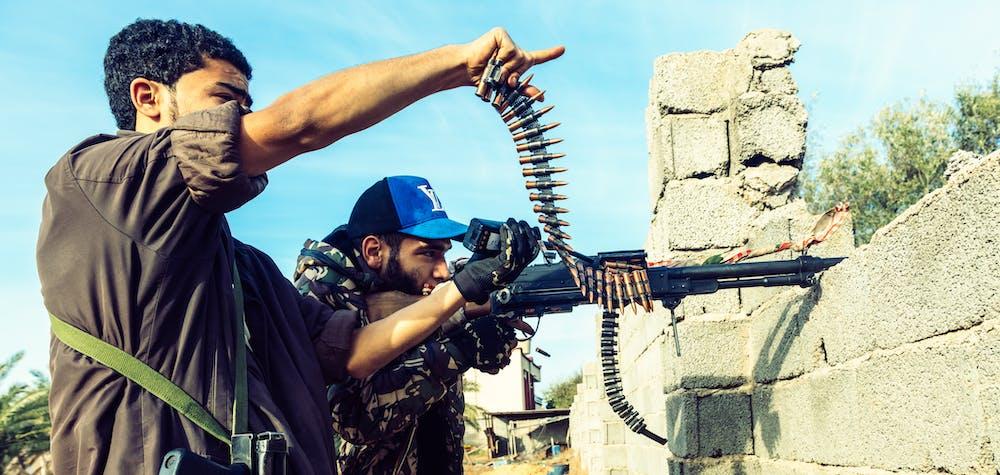 Sur la ligne de front de Al Swani pendant les affrontements, un combattant de la brigade 610 (GAN) tire avec sa mitraille alors que son camarade pointe du doigt l'ennemi. Depuis avril, l'armee nationale Libyenne (LNA) dirigee par Khalifa Haftar essaie de prendre le controôe de Tripoli defendu par les forces du gouvernement d'accord national de Fayez al-Sarraj, soutenu par l'onu (GAN). Libye, banlieue de Tripoli, 6 decembre 2019.
