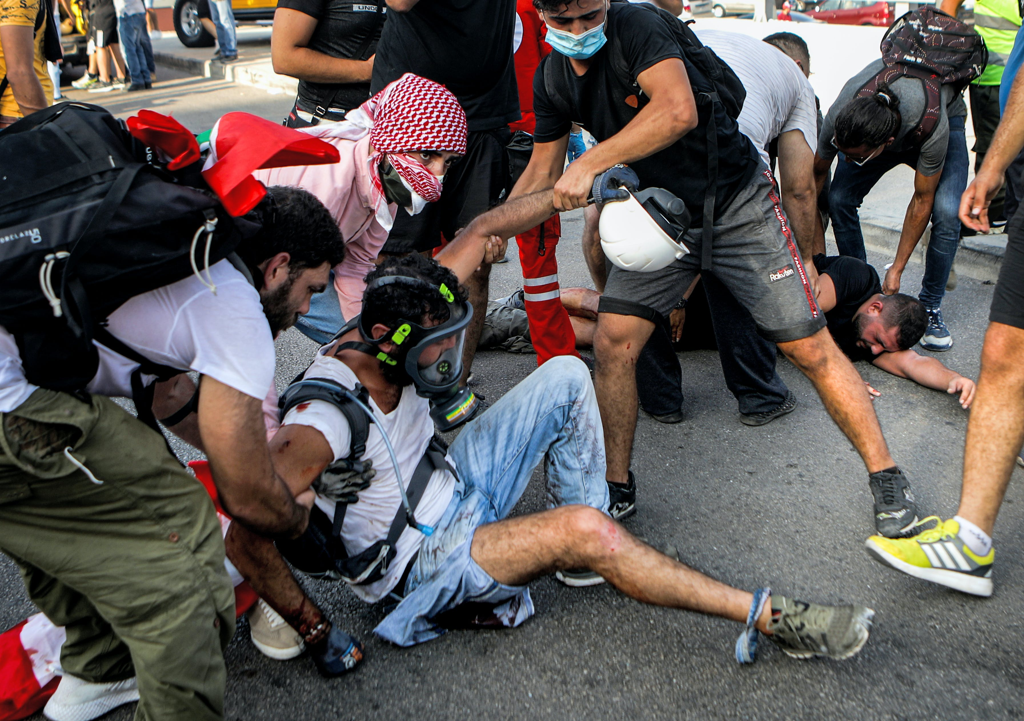 Lebanese protesters help a wounded demonstrator during clashes in downtown Beirut on August 8, 2020, following a demonstration against a political leadership they blame for a monster explosion that killed more than 150 people and disfigured the capital Beirut.