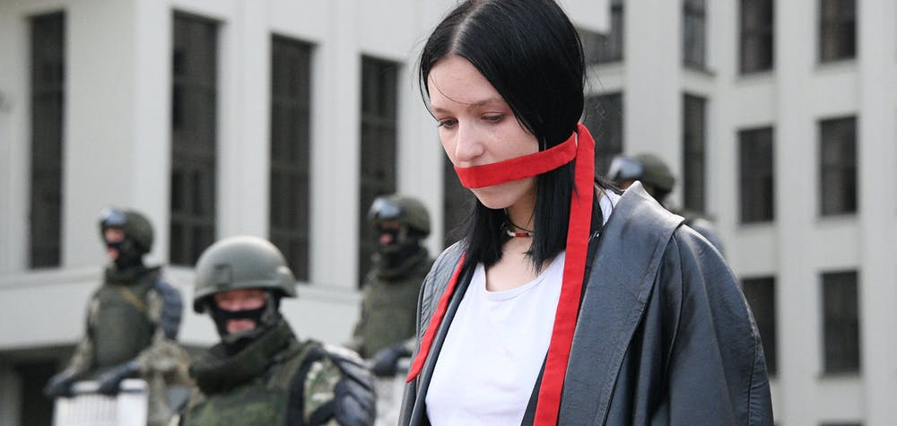 6308398 14.08.2020 A woman stands in front of members of Belarusian Interior Ministry troops as she attends an opposition demonstration to protest against police violence and to reject the presidential election results near the Government House in Independence Square in Minsk, Belarus. Viktor Tolochko / Sputnik