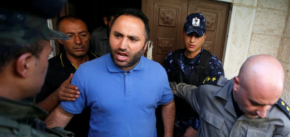 Activist Issa Amro is escorted by members of Palestinian security forces as he leaves a court in the West Bank city of Hebron September 7, 2017. REUTERS/Mussa Qawasma