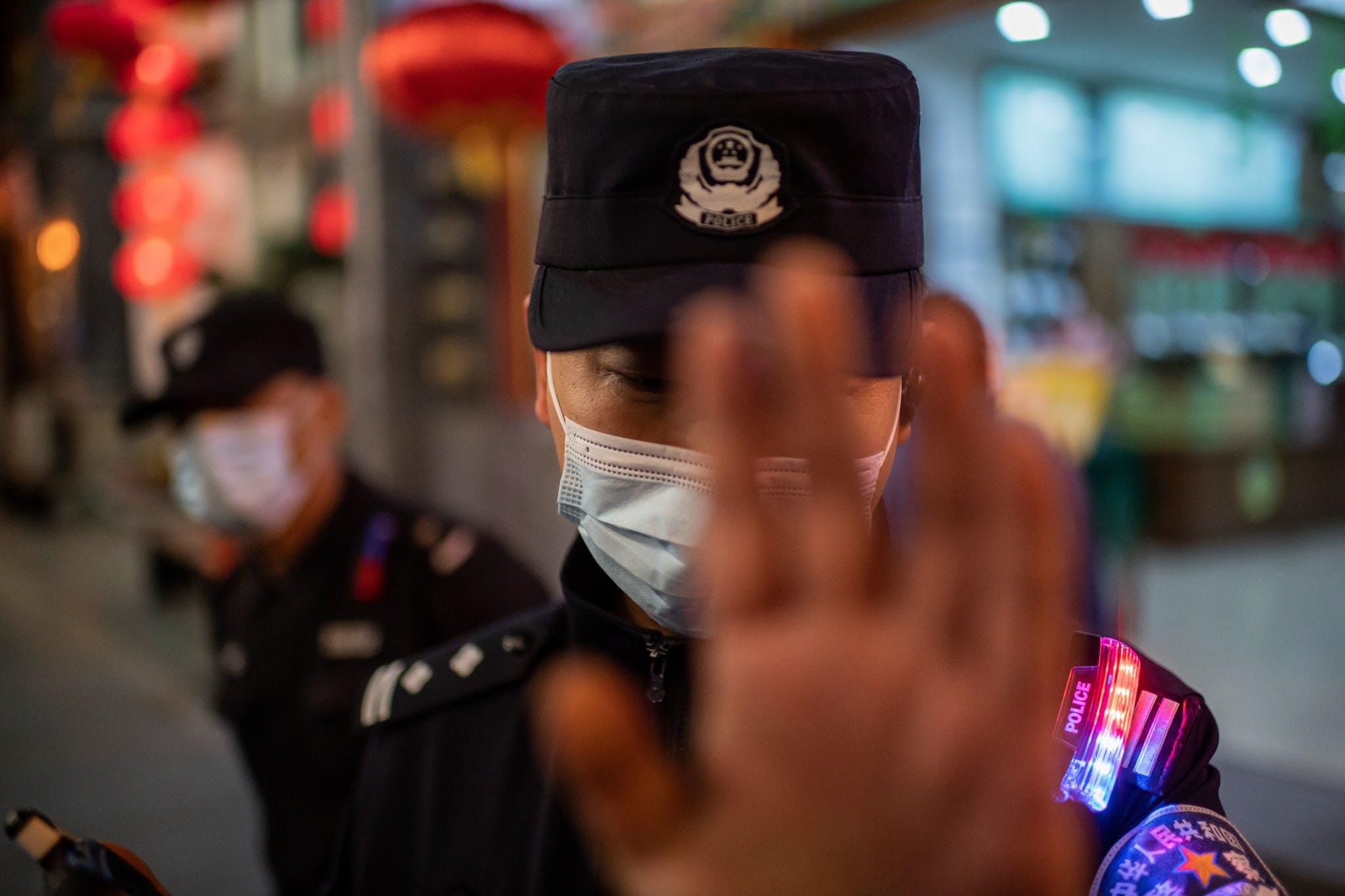 Un agent de police portant un masque facial par mesure de prévention contre le Covid-19 (nouveau coronavirus) tente d'empêcher un photojournaliste de prendre des photos dans une rue à l'extérieur d'un complexe commercial à Pékin, le 13 octobre 2020.