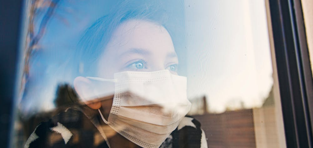 Young girl with mask looking through window