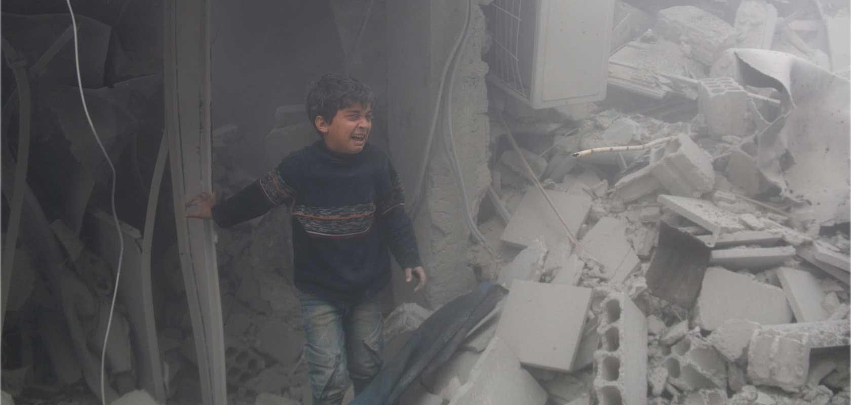 Jeune garçon dans les décombres après un bombardement sur Arbin. 20/02/2018  © Ammar Al Bushy/Anadolu Agency/Getty Images