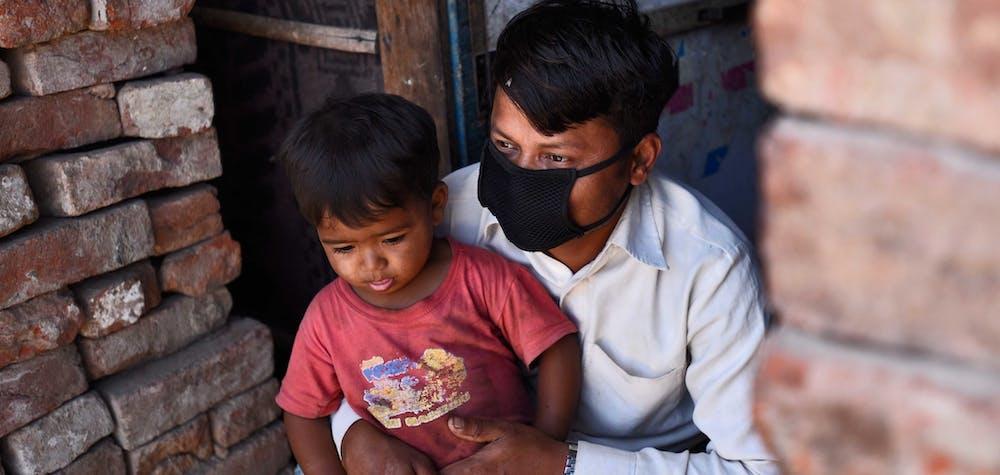 Un réfugié rohingya portant un masque protecteur se trouve à l'extérieur de son domicile temporaire alors que de la nourriture gratuite est distribuée par People for Social Development en collaboration avec la police de Delhi, le 15e jour de l'emprisonnement national de 21 jours pour freiner la propagation du coronavirus, à Okhla en avril. 8, 2020 à New Delhi, Inde.