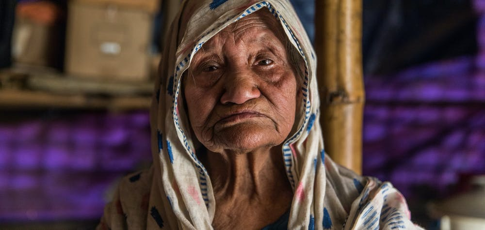 """Sokhina Khatun, a Rohingya woman around 90 years old, stands for a portrait in her shelter in Camp #1 East (Kutupalong Camp), Bangladesh, 19 February 2019.  """"I've fled [from Myanmar] four times in my life,"""" she told Amnesty International. """"The fourth time was in 2017. I came here with only my walking stick [and] this thami (longyi)… There has never been peace for us. We've had to flee here frequently. We were under persecution for so long.""""  """"My number one problem [in the camp] is the latrine. The latrine is down at the bottom [of the hill], it's very difficult for me to go down there. Sometimes I just go inside [my shelter in a pan]… I've been surviving like that."""""""