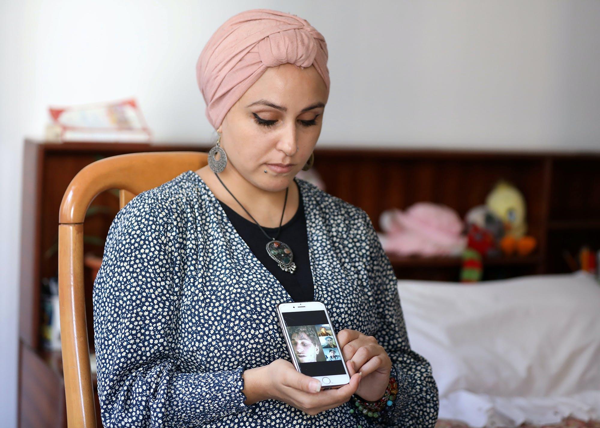 Fida Al Waer, une artiste et enseignante syrienne vivant à Beyrouth, pose en tenant un téléphone portable sur lequel s'affichent des photos de son frère qui, selon elle, a été identifié parmi des milliers d'images, sorties clandestinement de Syrie par un ancien photographe militaire syrien