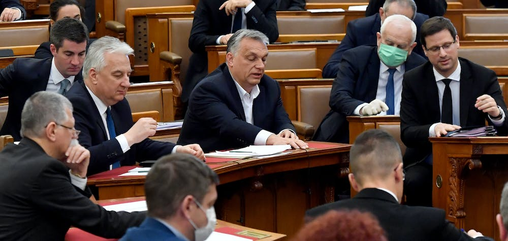 Hungarian Prime Minister Viktor Orban (C) votes with other representatives about the government's bill on the protection against the new coronavirus COVID-19 at the plenary session of the Hungarian Parliament in Budapest, Hungary on March 30, 2020.