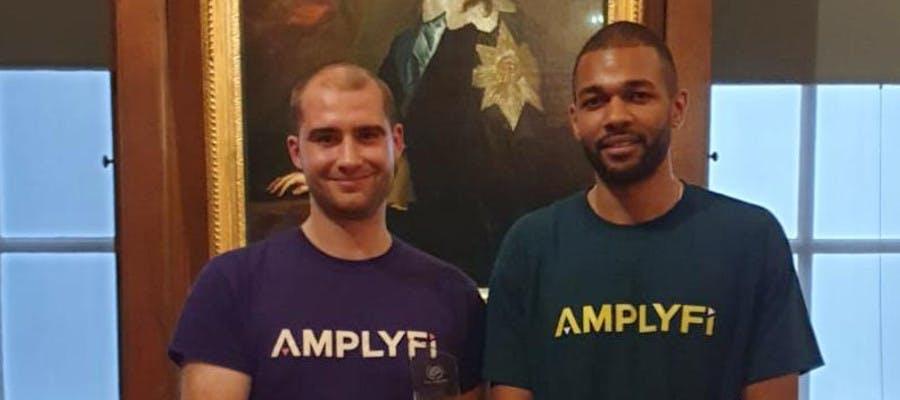 Two men in AMPLYFI t-shirts holding an award trophy