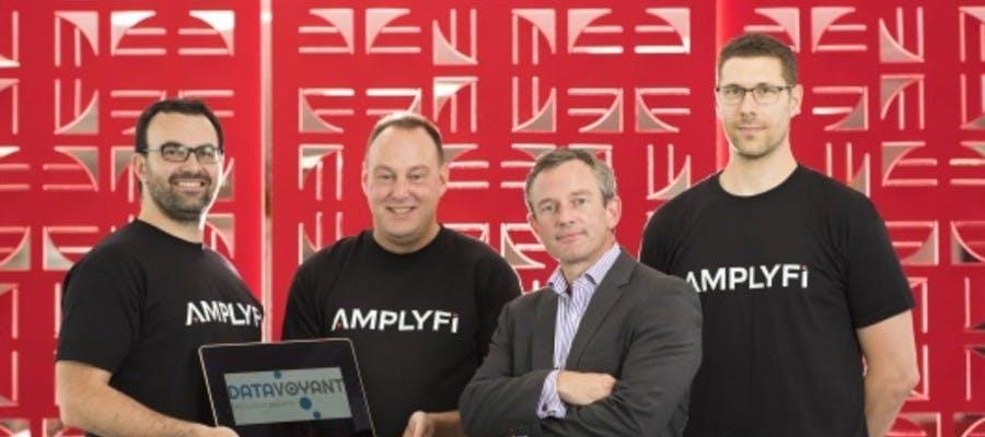 A group of four men, three wearing AMPLYFI t-shirts