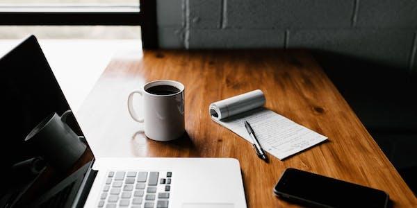 Mesa con ordenador taza de café móvil y notas