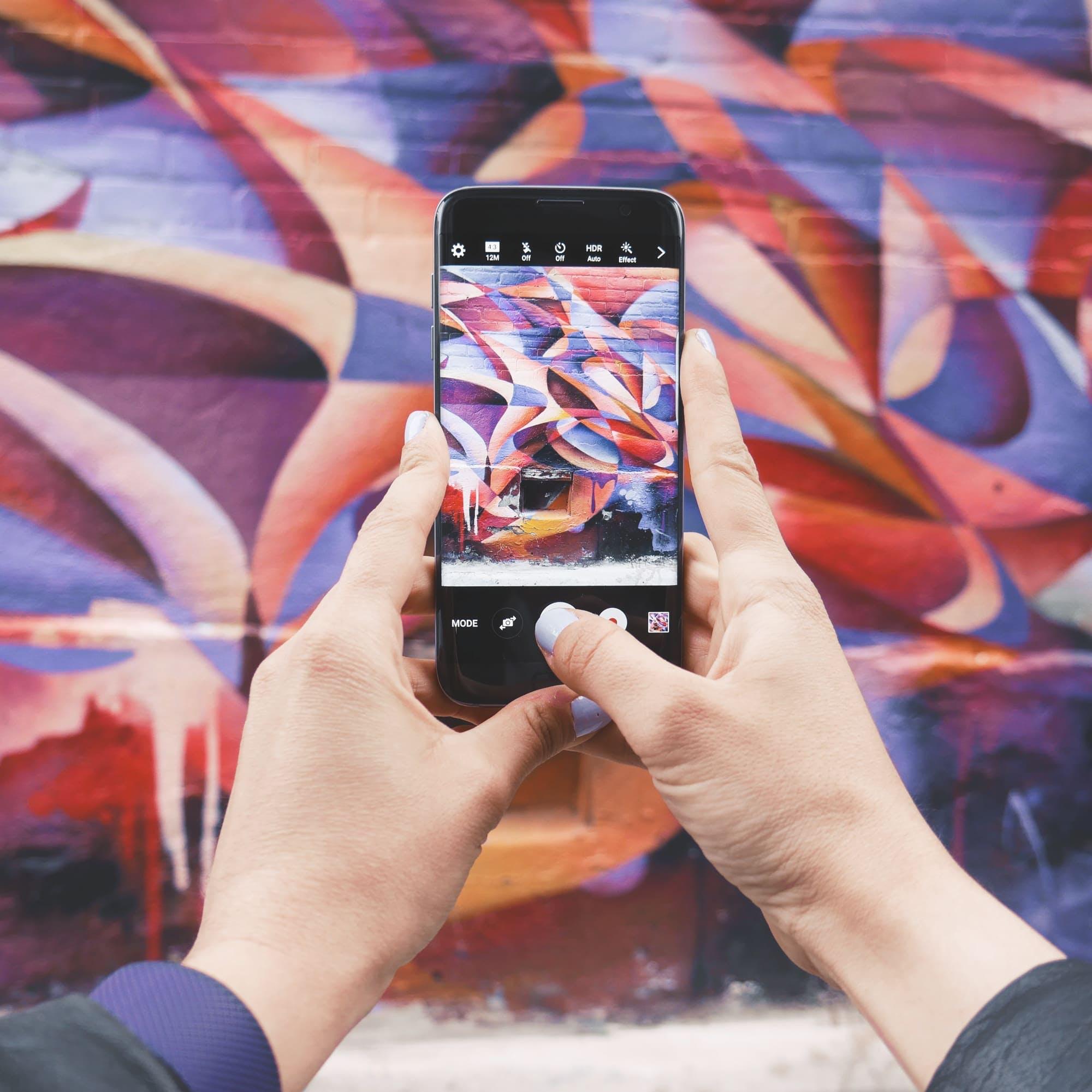 alguien sacando fotos de una pared con el teléfono