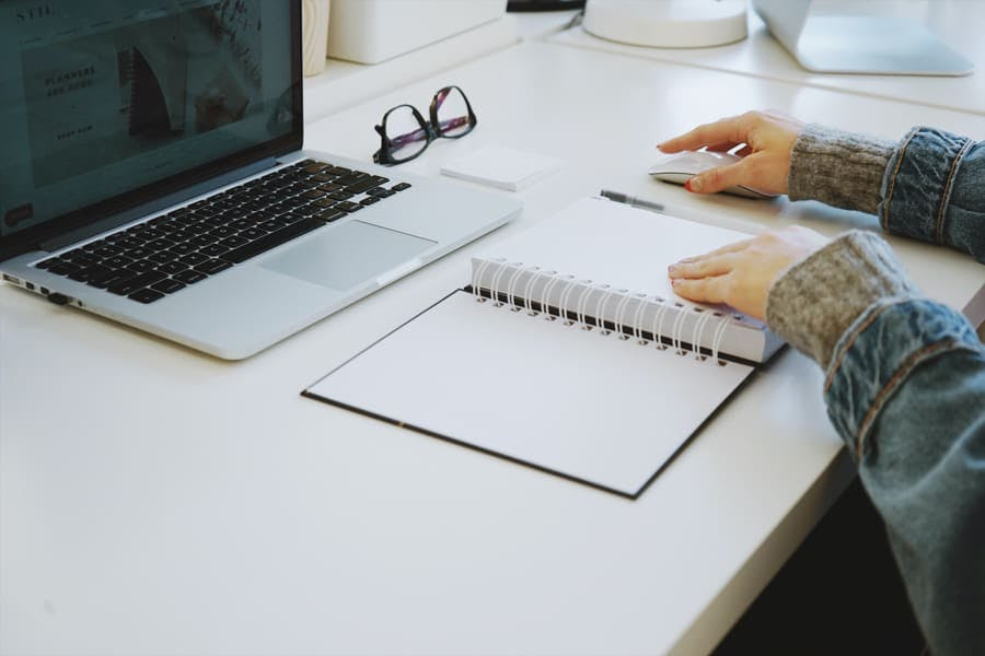 Cuaderno y laptop en un escritorio blanco