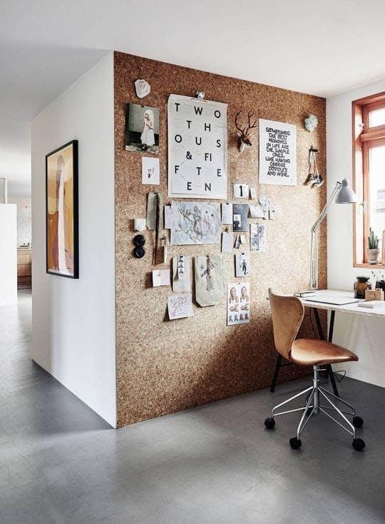 Un espacio de trabajo con una pared de corcho con un vision board