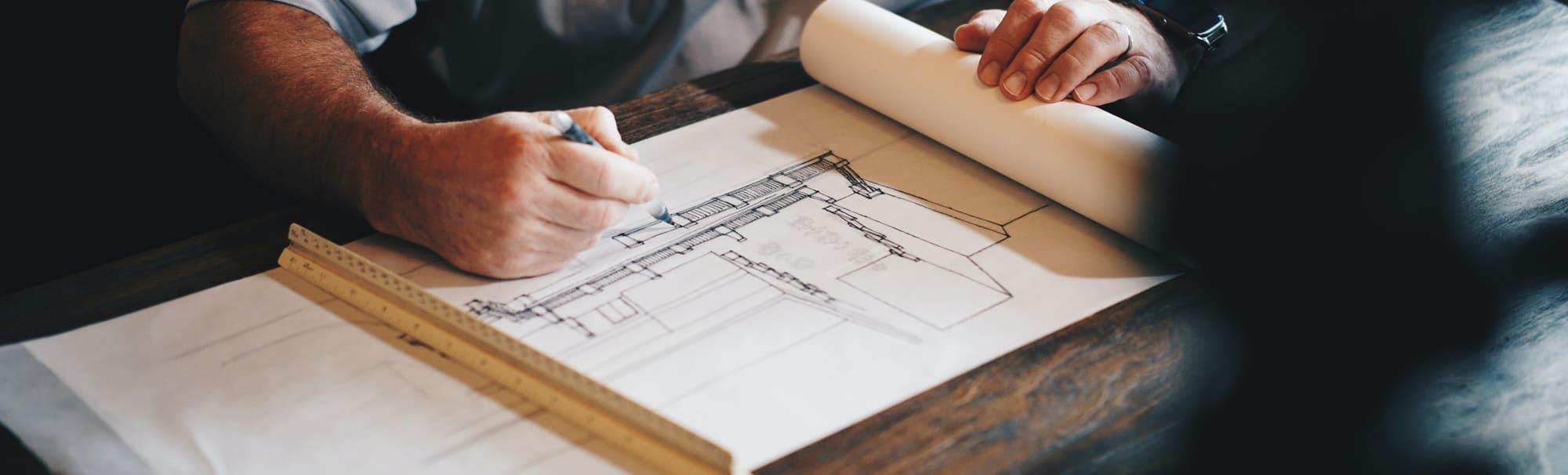 manos dibujando un edificio