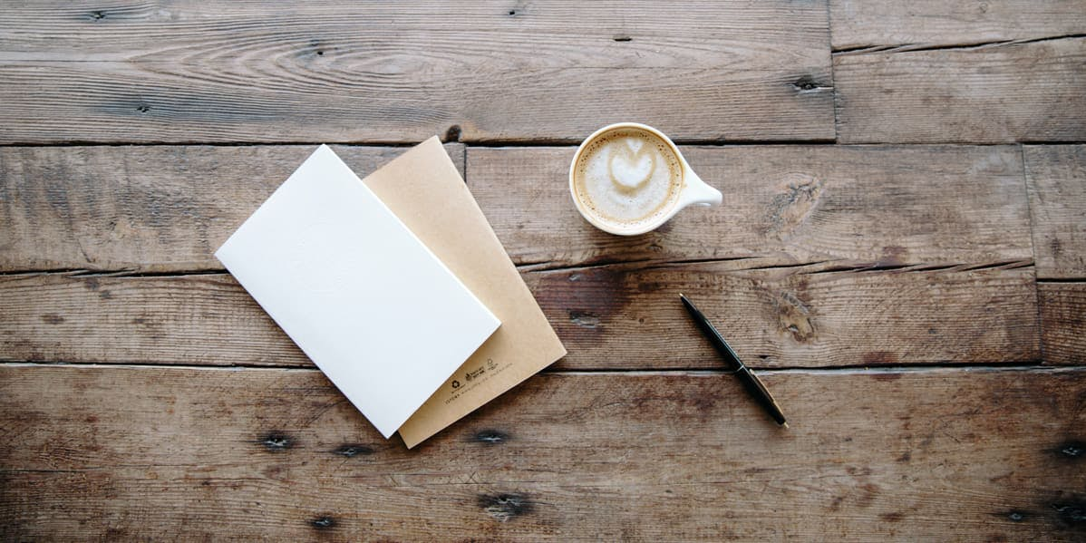 carta en blanco en una mesa de madera y café