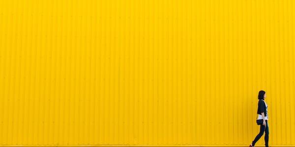 mujer delante de pared alta amarilla