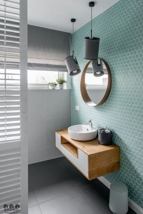 Baño con mueble suspendido, espejo redondo y lámpara colgante