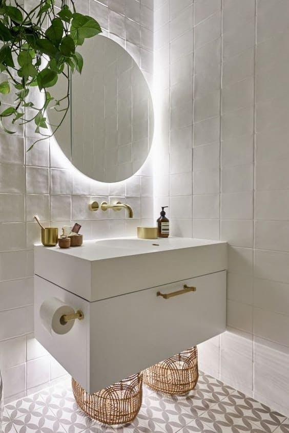 Baño en blanco con espejo redondo y mueble suspendido iluminado