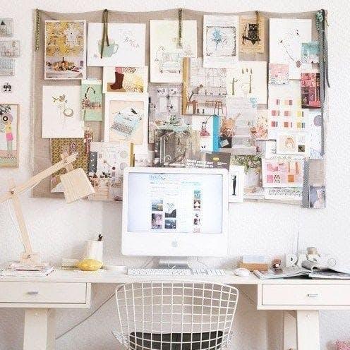 Un escritorio con un vision board en la pared