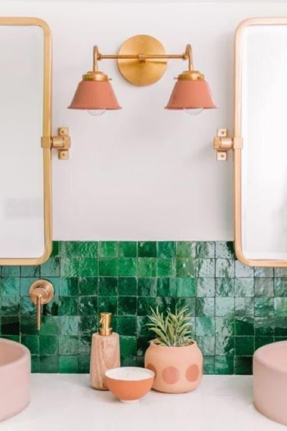 Baño con azulejo verde y lavabos rosa