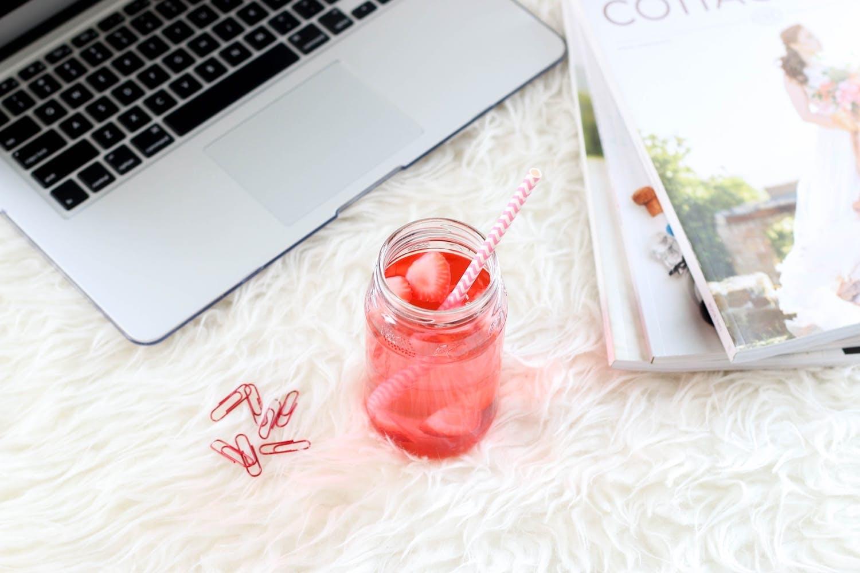 un zumo rojo un portátil revistas y clips