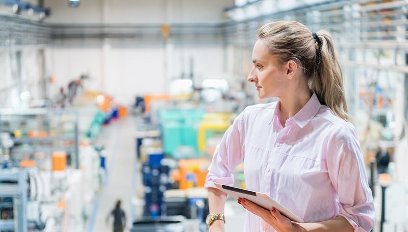 Woman with tablet overlooking industrial setting