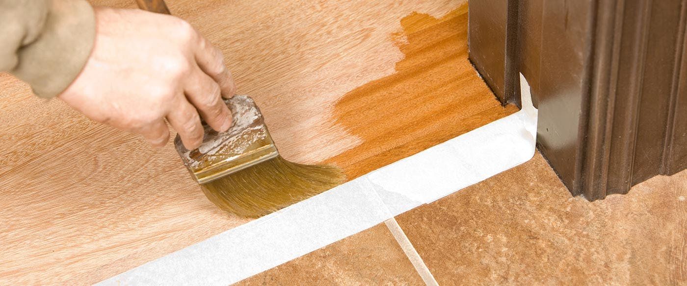 Using a paintbrush to apply a coat of finish to chemically buffed hardwood floors around baseboards and the edges of the room.